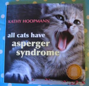 [Image description: the cover of All Cats Have Asperger Syndrome, which features a grey tabby kitten with an open mouth. A sticker indicates that the book was shortlisted by the Children's Book Council of Australia.]